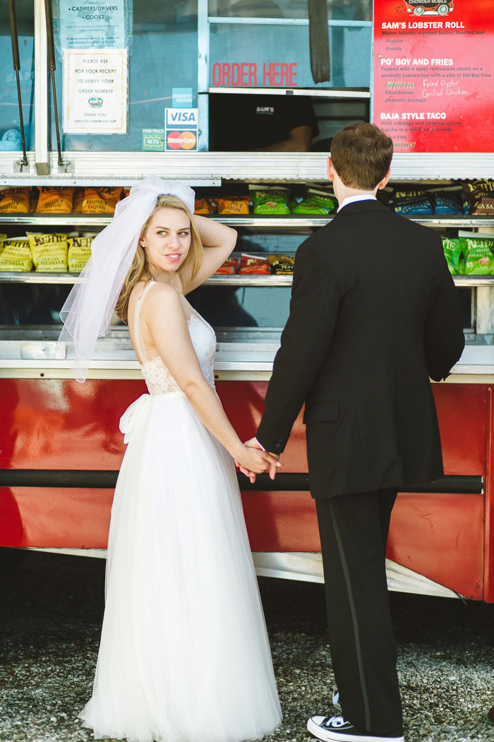 bride and groom standing in front of food truck