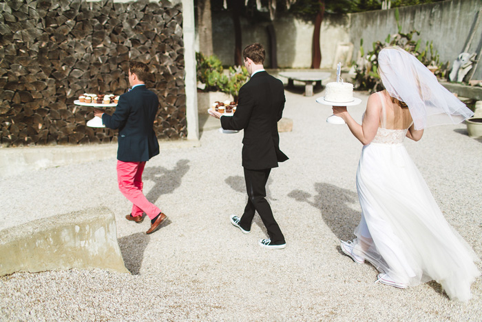 bride and groom and officiant carrying cakes