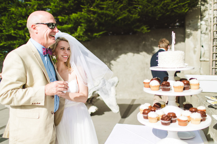 bride looking at wedding cake with her dad