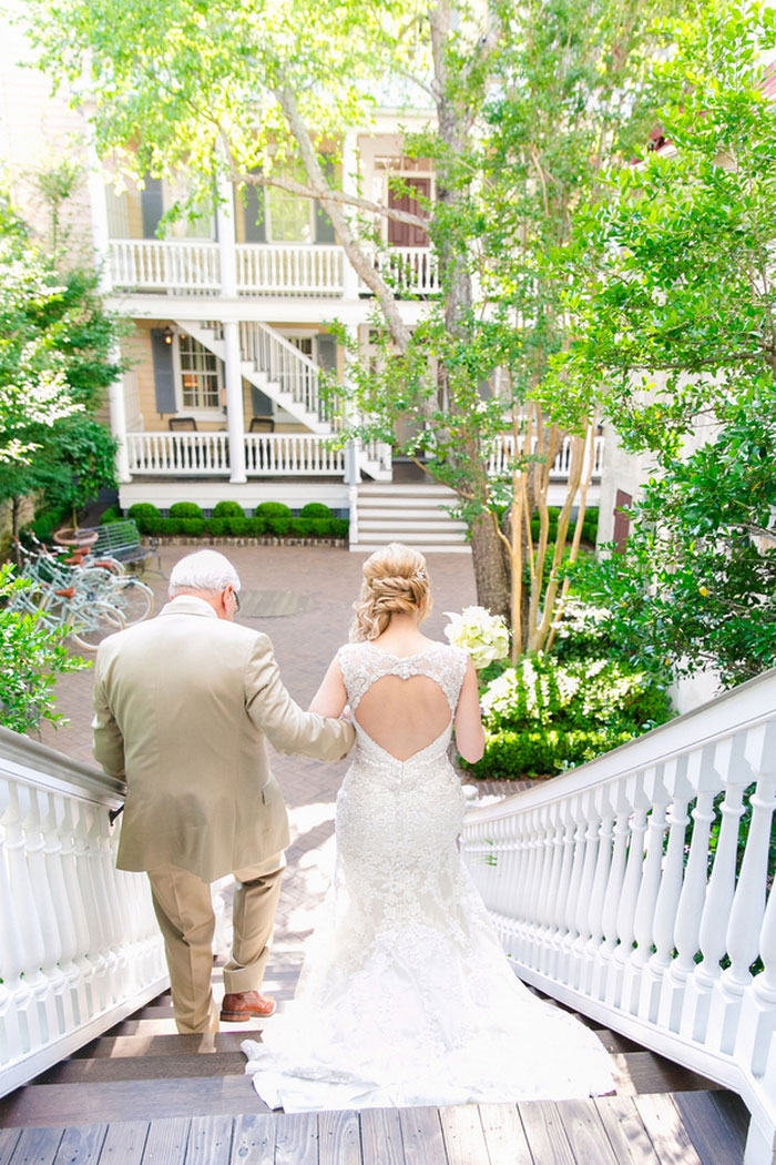 bride waking down outdoor stairs with father