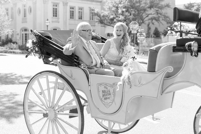 bride laughing in horse drawn carriage with her dad