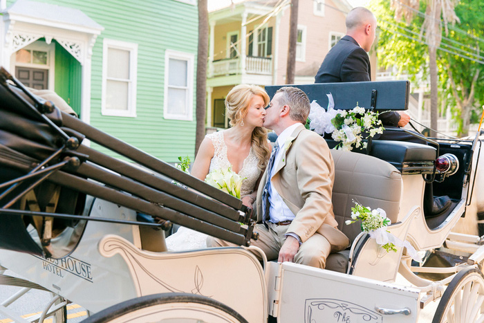 bride and groom kissing in carriage