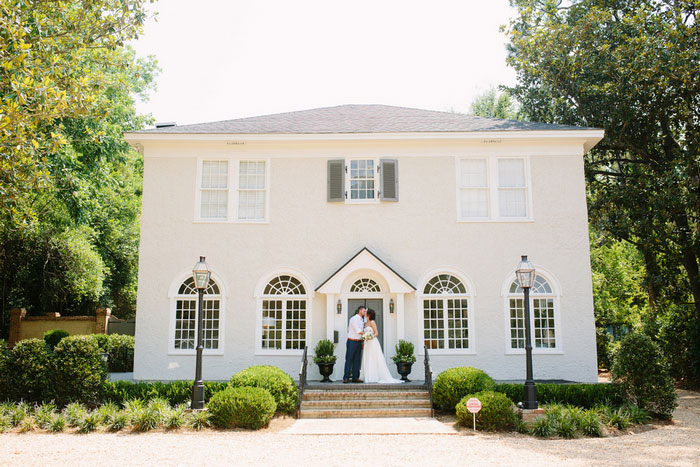 bride and groom portrait in front of house