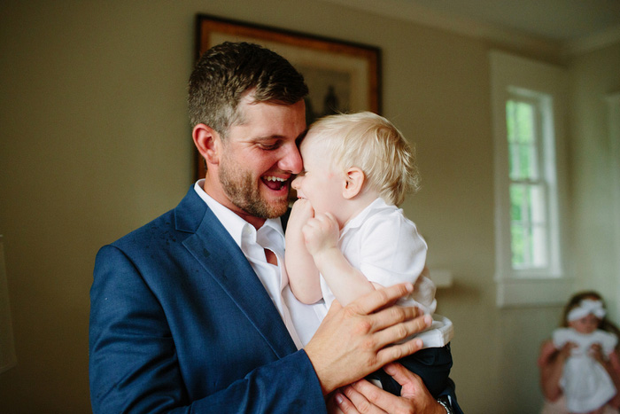 groom laughing with baby son
