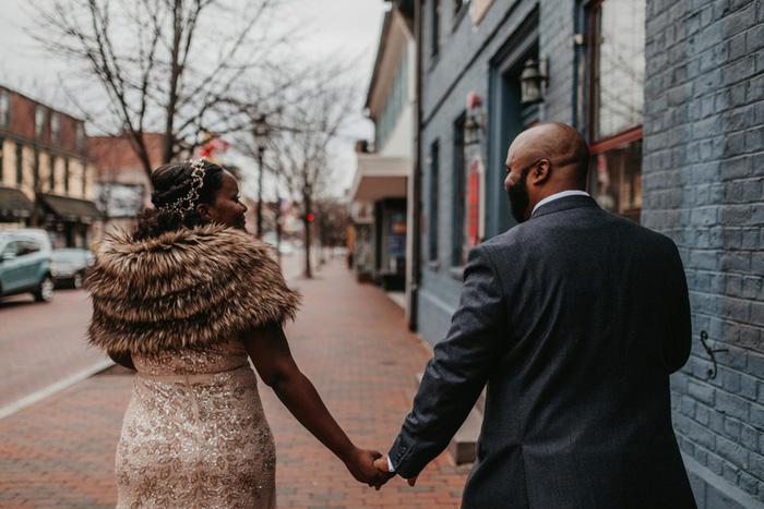 bride and groom walking down street holding hands