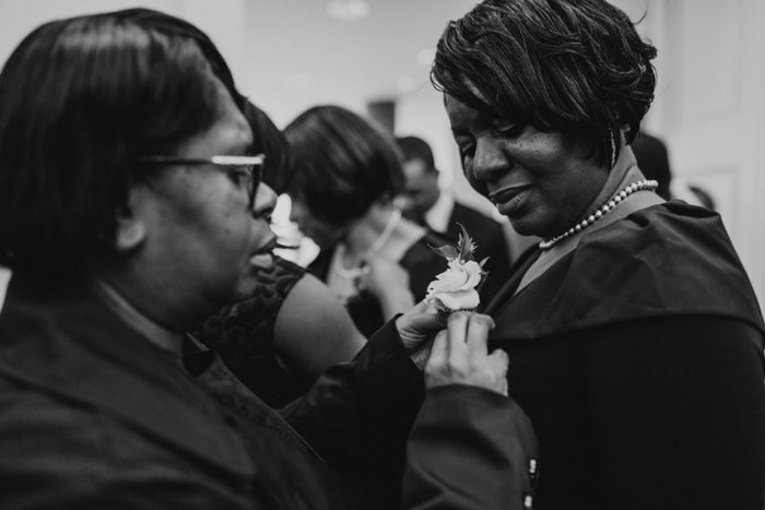 boutonniere being pinned onto dress
