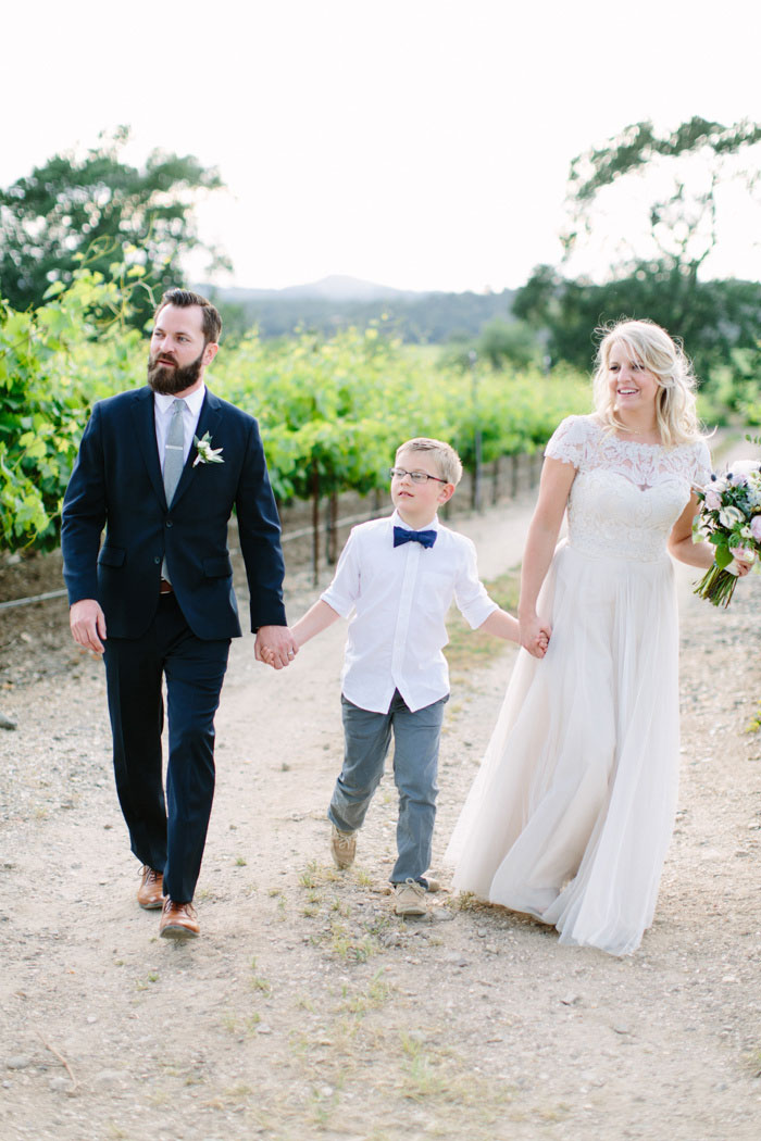 bride, groom and son, walking down dirt road