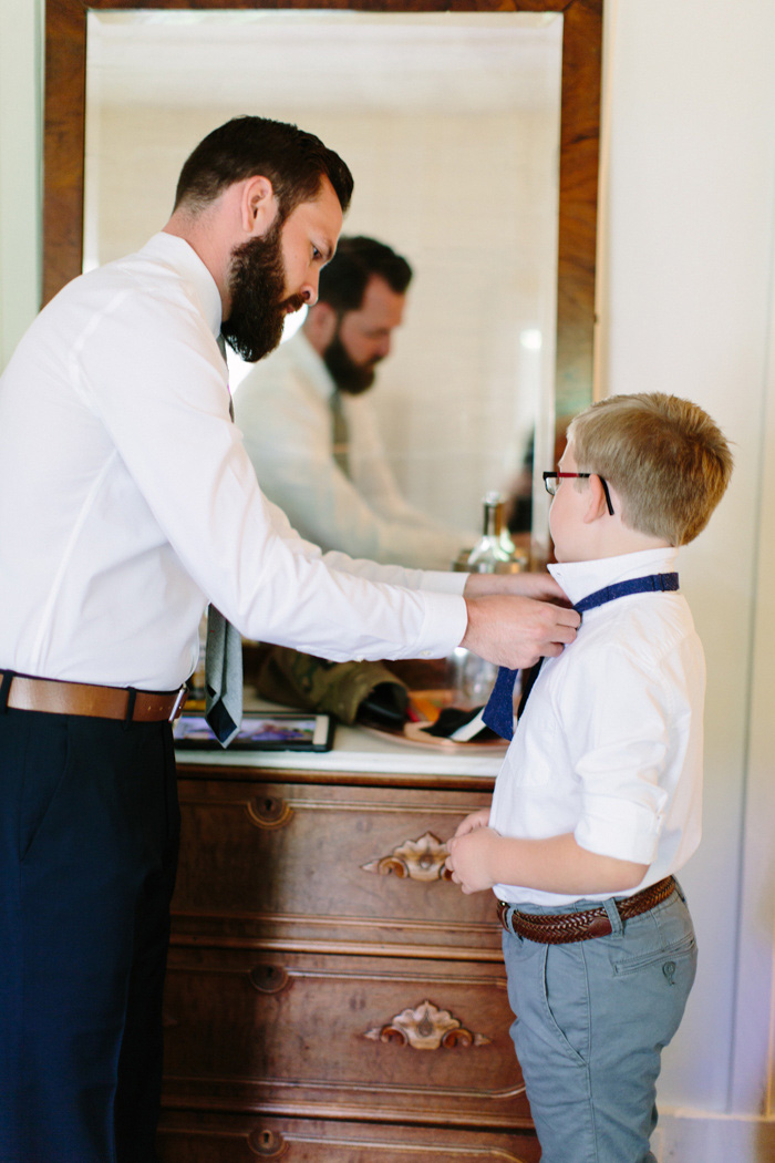 groom tying son's bow tie