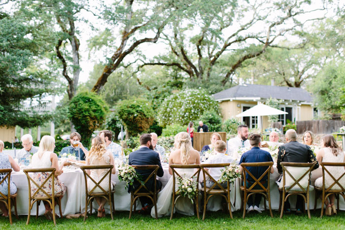 wedding guests seated out large outdoor table