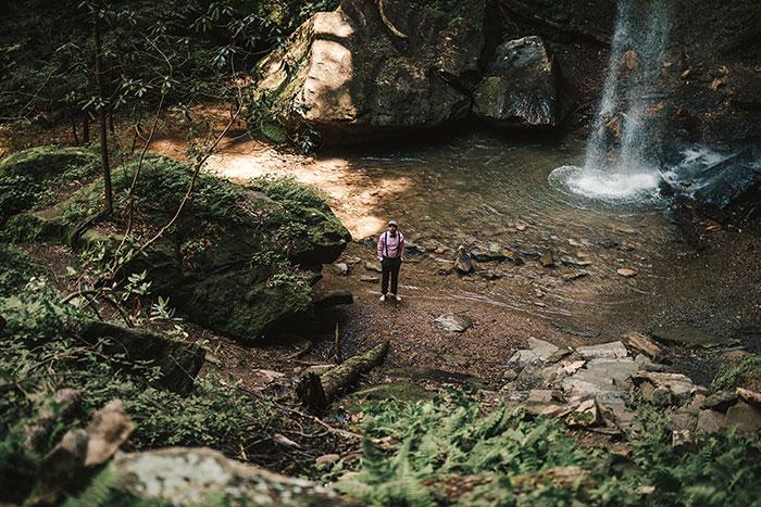 groom waiting at base of waterfall