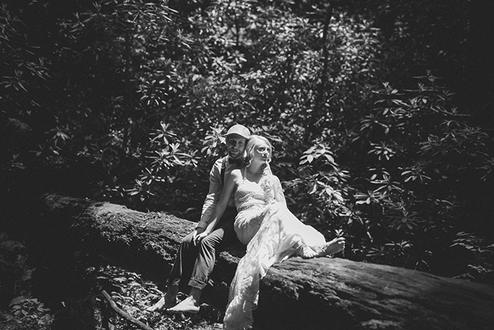 bride and groom sitting on log