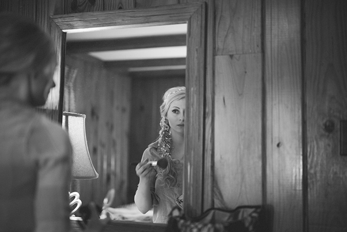 bride taking a photo in the mirror
