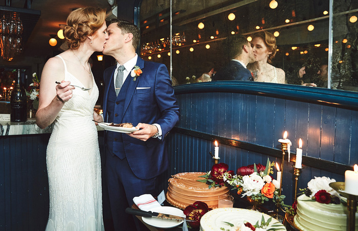 bride and groom kissing after cutting cake