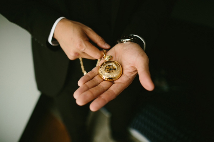 gold pocket watch in groom's hand