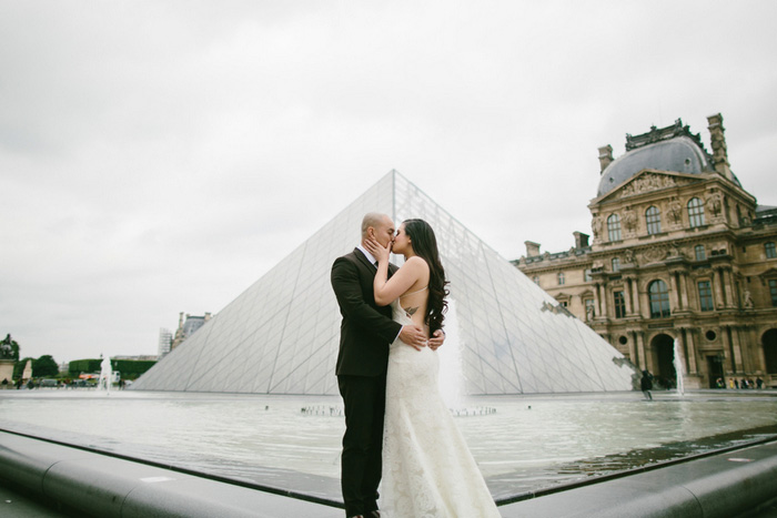 Bride and Groom kissing in front of the Louvre