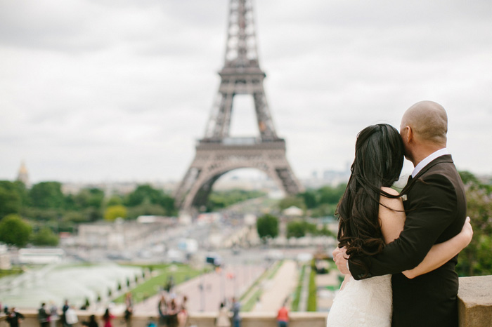 bride and groom looking at the eiffel tower