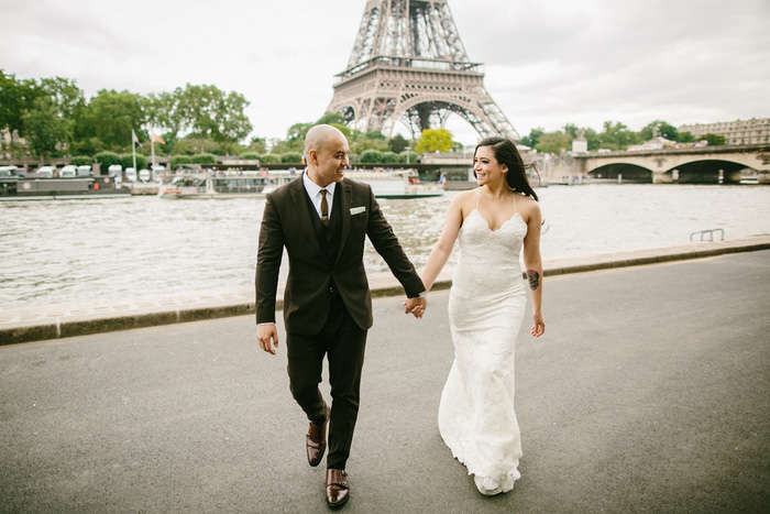 bride and groom walking away from Eiffel Tower