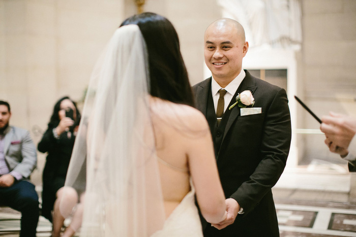 groom grinning at bride during ceremony