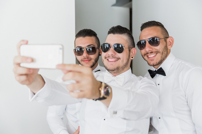 groom taking selfie with his groomsmen
