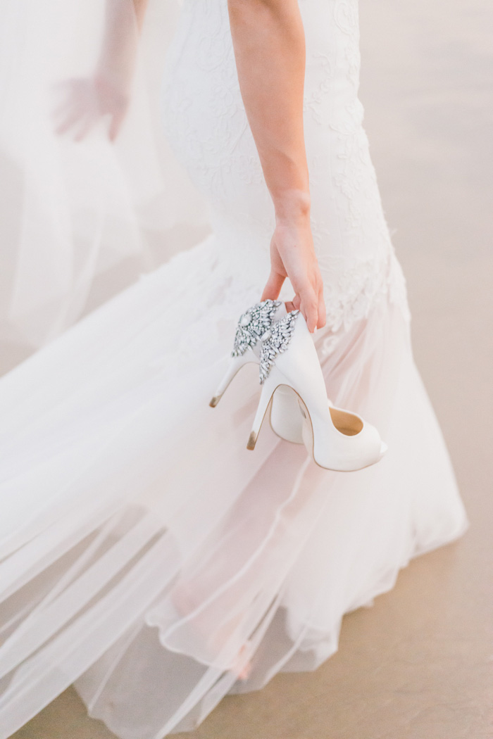 bride carrying shoes on the beach
