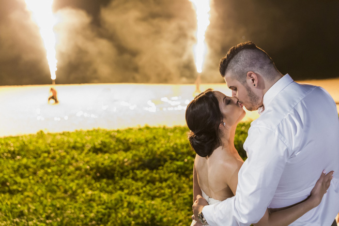 bride and groom kissing wth fireworks