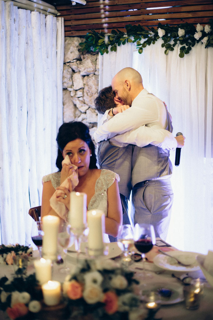 bride wiping away tear as groom and son hug