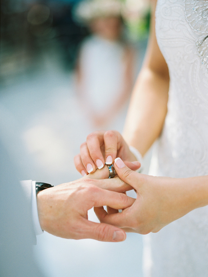 bride putting ring on groom's finger