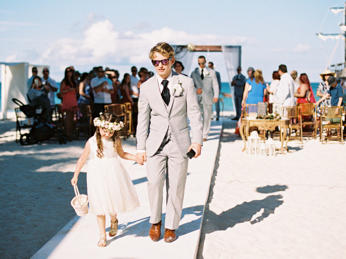 flower girl and groomsman walking down aisle