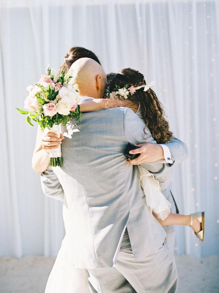 groom hugging bride and daughter