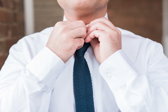 groom adjusting tie